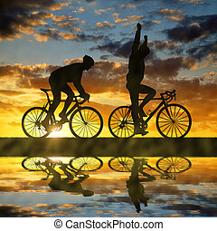 Silhouette of two cyclists riding a road bike at sunset