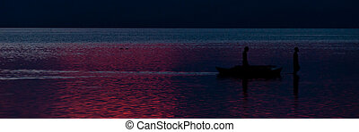 Silhouette of Two Fishermen Out In The Sea at blue purple sunset