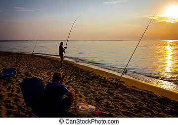 Silhouette of two friends who are fishing on the beach in sunrise morning