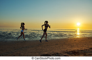two girl running by the sea on the beach