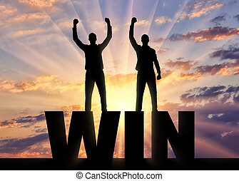 Silhouette of two happy men with raised arms standing on the word win.
