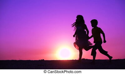 silhouette of two kids runniing at sunset