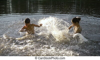 silhouette of two kids splashing water in pond at sunset