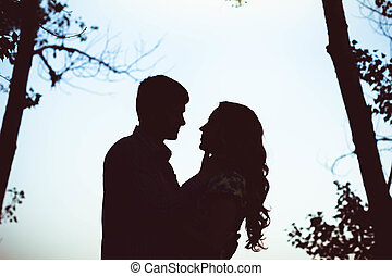 Silhouette of two lovers embracing in the forest.