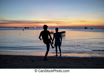 silhouette of two man playing football on sea beach against sunset sky
