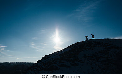 Silhouette of two men standing on the cliff, deep blue sky background