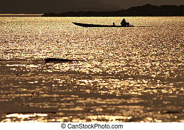 silhouette of two people rowing a boat in the river