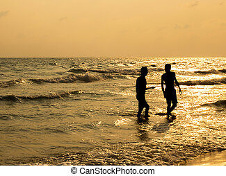silhouette of two people walking on beach