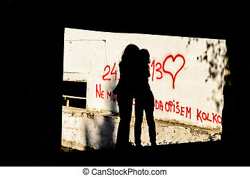 Silhouette of two seven year old little girls hugging