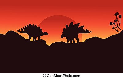 Silhouette of two stegosaurus on the cliff