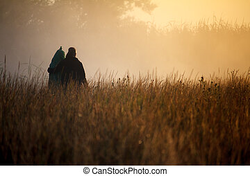 Silhouette of two travelers against fog landscape over a flower meadow, the first rays of dawn and dark silhouettes of trees against a sunrise, selective focus