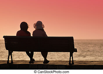 Silhouette of two women on a bench