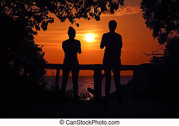Silhouette of two women standing watching the sunset on the viewpoint