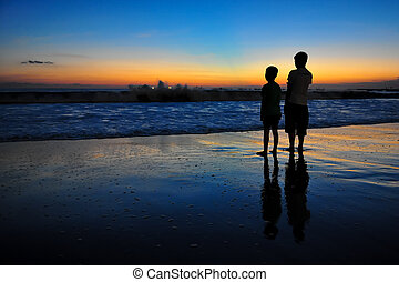 Silhouette of two young boys at ocean sunset