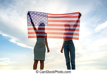 Silhouette of two young friends women holding USA national flag in their hands at sunset. Patriotic girls celebrating United States independence day. International day of democracy concept.