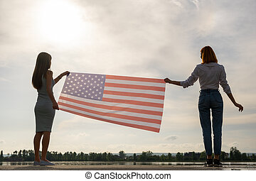 Silhouette of two young friends women holding USA national flag in their hands at sunset. Patriotic girls celebrating United States independence day.