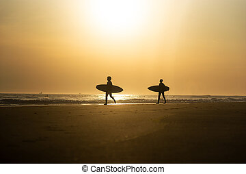 Silhouette of two young men with surfboards
