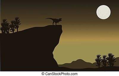 Silhouette of tyrannosaurus in cliff with moon