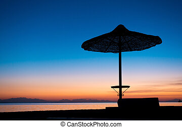 silhouette of umbrella on the beach in twilight