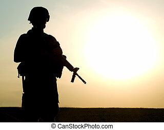US soldier - Silhouette of US soldier with rifle against a...
