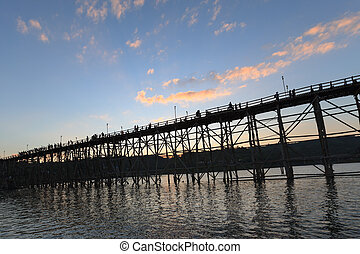 silhouette of Utamanusorn Bridge (Mon Bridge), made from wooden for across the river in Sangkhlaburi District, Kanchanaburi Thailand and blue sky