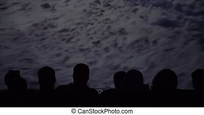 Silhouette of viewers in the cinema while watching a...