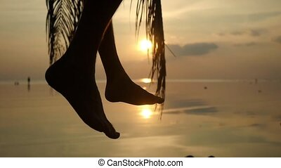 Silhouette of waving male legs at tropical beach during beautiful sunset. Young man sits on a palm tree. Slow motion. 1920x1080