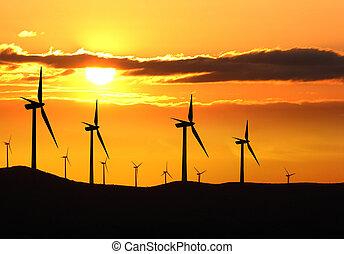 Silhouette of wind turbine farm over sunset