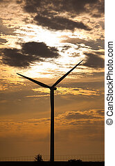 Silhouette of wind turbines against the sunset sky