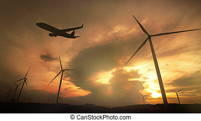 Silhouette of Windmills for electric power production and Airplane take off on the Colorful dramatic sky with cloud at sunset background