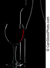 silhouette of wine bottle and glass over black
