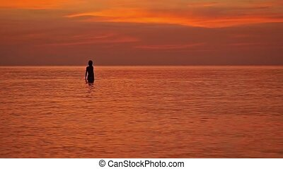 Silhouette of woman admire sunset in the sea, slow motion....