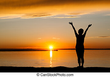 Silhouette of Woman at Golden Sunset With Copy Space