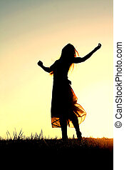 Silhouette of Woman Dancing and Praising God at Sunset - A...