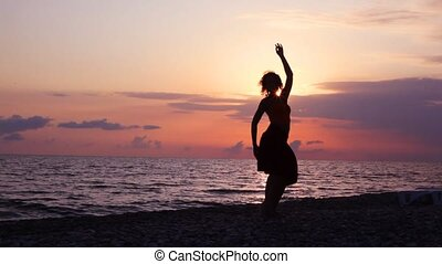 silhouette of woman dancing on beach, sunset sea and sky in background