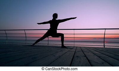 Silhouette of woman doing yoga Virabhadrasana Warrior Pose on wooden embankment. Stretching, practice, healthy lifestyle concept