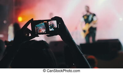 Silhouette of Woman Hands Making Video with Smartphone at Live Rock Concert. Slow Motion. Crowd of people at a music festival. Fans near stage are filming a concert. Live broadcast in social networks.