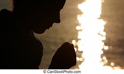 Silhouette of woman head, holding two fists together -...