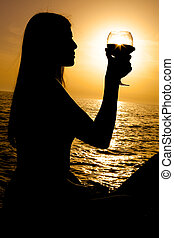 Silhouette of woman holding glass of wine during sunset on the ocean