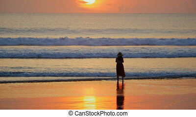 Silhouette of woman in hat at beach by the ocean. Woman standing in the waves and enjoying the beautiful sunset