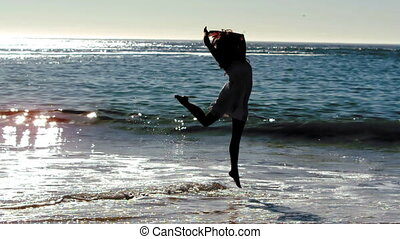Silhouette of woman jumping on the