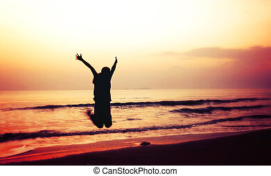 silhouette of woman jumping on the beach