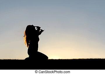 Silhouette of Woman Kneeling in Prayer and Surrender