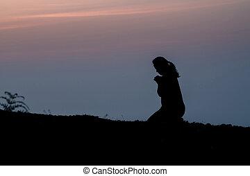 Silhouette of woman kneeling on mountain