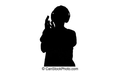 Silhouette of woman listening to mu
