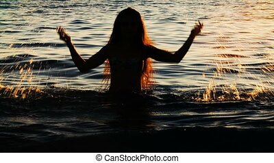 silhouette of woman making splashes with water. Travel...