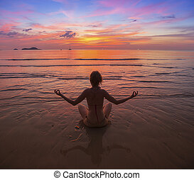 Silhouette of woman meditating on the sea beach.