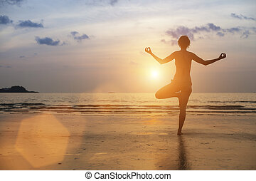 Silhouette of woman meditating on the sea beach. Yoga.