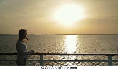 Silhouette of woman on deck of cruise ship at sunrise