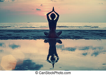 Silhouette of woman practicing yoga during sunset at the seaside.